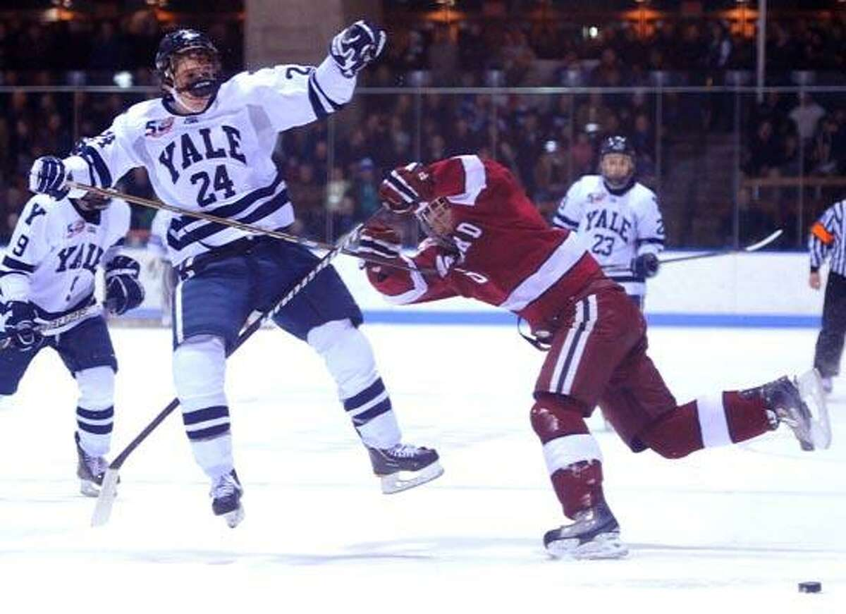 New Haven--Yale's Chris Cahill and Harvard's Ryan Grimshaw battle during the first period of Friday night's game at Ingalls Rink. Photo by Brad Horrigan/New Haven Register-02.04.11.