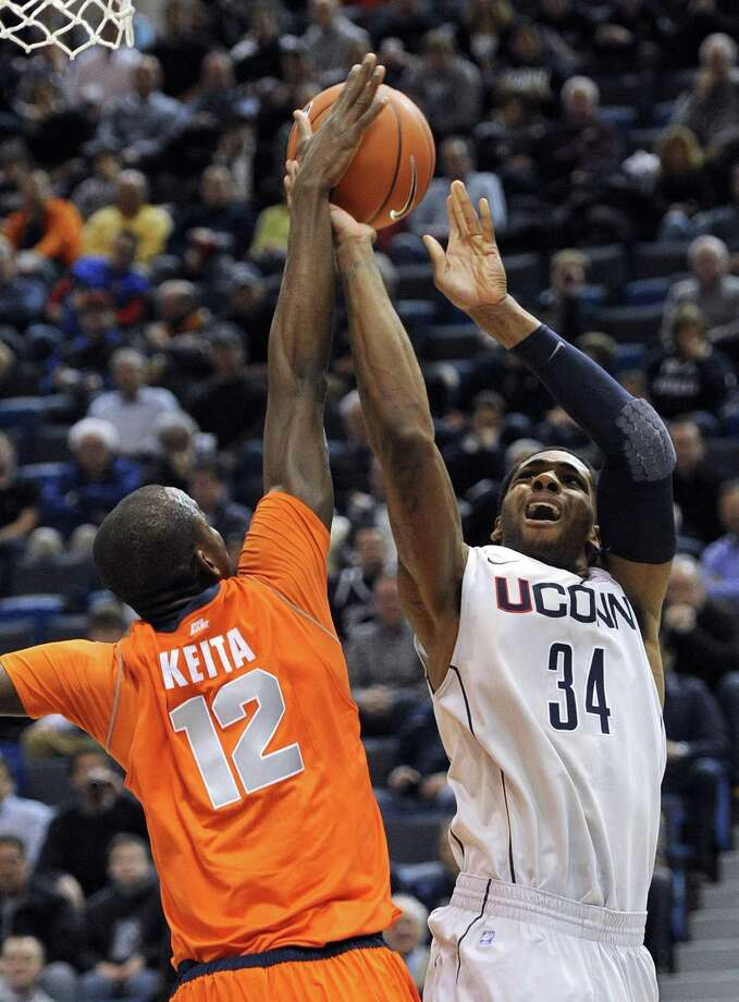 Syracuse's Baye Moussa Keita (12) blocks a shot attempt by Connecticut's Alex Oriakhi during the first half of an NCAA college basketball game in Hartford, Conn., Wednesday, Feb. 2, 2011. (AP Photo/Jessica Hill) Photo: AP / FR125654 AP