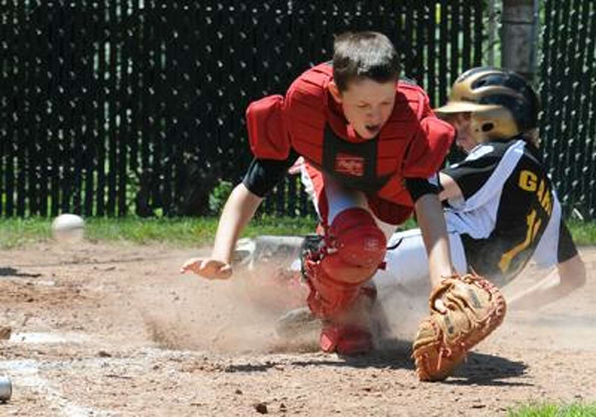 Fairfield American catcher Connor Daley can't get the throw in time as Madison's Ryan Garb slides in safely at home Saturday in Bridgeport. Fairfield American won 15-4. The two teams will play again Sunday. (Mara Lavitt/Register)
