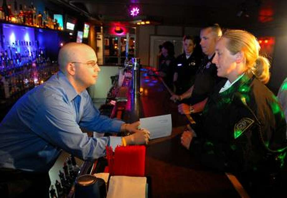 Police Lt. Rebecca Sweeney, right, talks with Andrew Behm, manager of Static on Crown Street, after looking at the club's liquor license. Everything checked out at Static Friday night. (Brad Horrigan/Register)