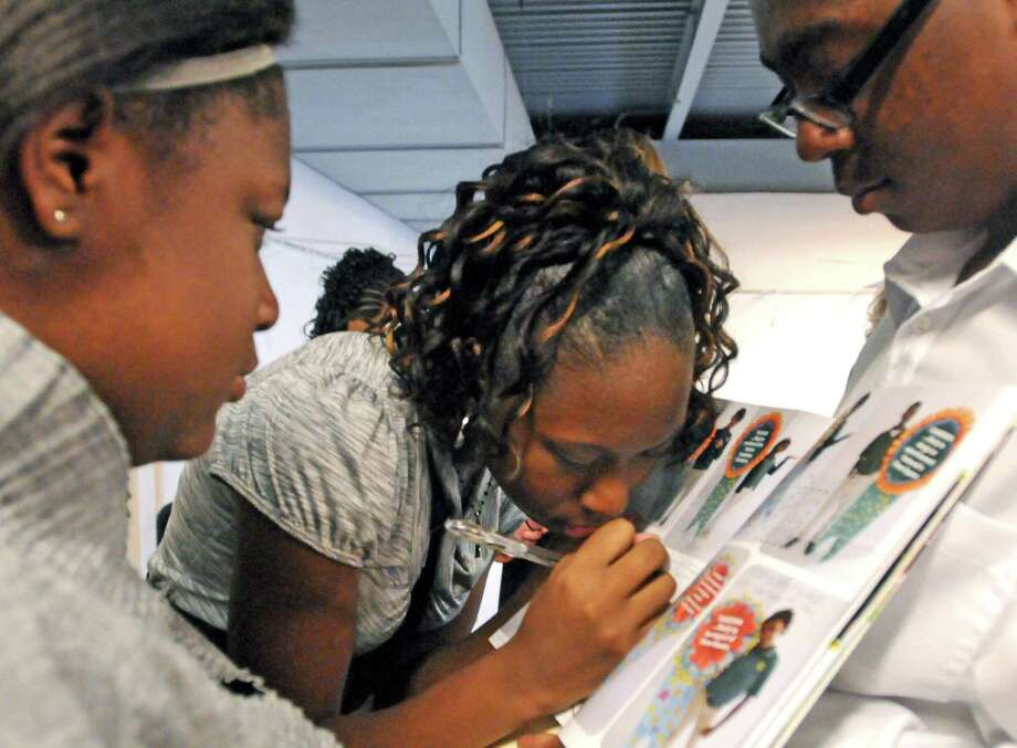 Tanazeia Marks, center, signs a yearbook for classmate Nykese Thomas, right, as Alaysia Browne looks on, left, before the three eighth graders start their commencement exercises  graduating from the Elm City College Preparatory Middle School. The graduation ceremony was held at the Long Wharf Theatre. All three students are from New Haven. Photo by Peter Hvizdak