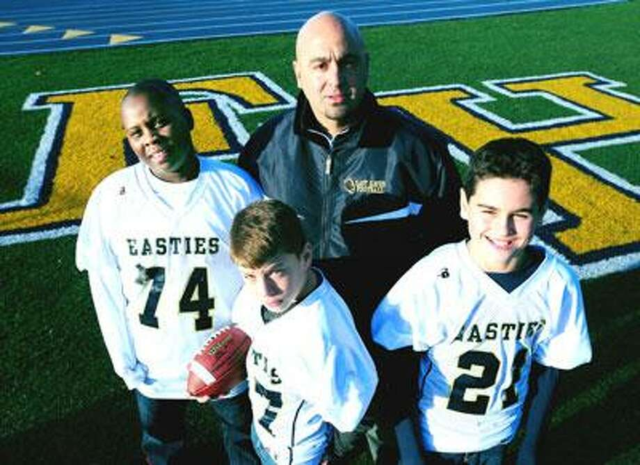 East Haven sixth-grade football coach Gianni Ragaini (center) is photographed with his players Trevon Pue (left), Corey Millhouse (center front) and Nico Ragaini (right) at East Haven High School. (Arnold Gold)