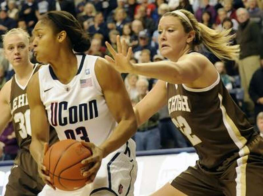 Connecticut's Maya More, left, looks for a teammate to pass to as Lehigh's Emily, right, guards her in the first half of an NCAA college basketball game at Storrs, Conn., Saturday, Nov. 27, 2010.  (AP Photo/Bob Child) Photo: AP / FR170410 AP