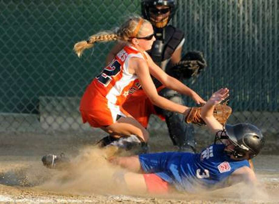 Clare Hurley of Waterford slides safely into home as Orange pitcher Katie Koshes covers and Orange catcher Hayley Kober looks on during the fifth inning of Waterford's 7-1 win Tuesday at Whiteley Field in Jewett City. (Peter Hvizdak/Register)