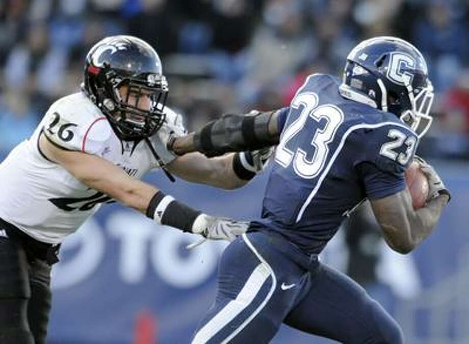 Connecticut's Jordan Todman, right, elludes a tackle attempt by Cincinnati's Drew Frey in the second half of Connecticut's 38-17 victory in their NCAA football game in East Hartford, Conn., on Saturday, Nov. 27, 2010. Todman rushed for 175 yards and had three touchdowns in the victory.(AP Photo/Fred Beckham) Photo: AP / FR153656 AP