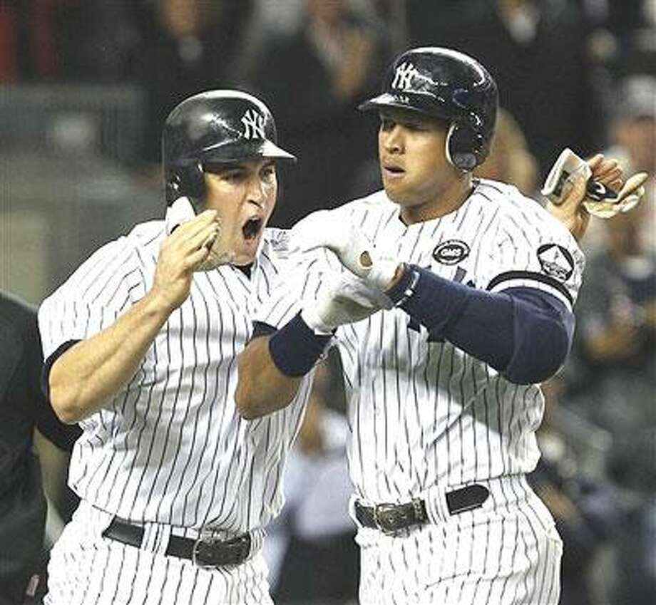 New York Yankees Mark Teixeira, left, celebrates with Alex Rodriguez after scoring on Rodriguez's seventh-inning two-run, home run off Boston Red Sox starter Daisuke Matsuzaka in their baseball game at Yankee Stadium in New York, Sunday, Sept. 26, 2010. (AP Photo/Kathy Willens)
