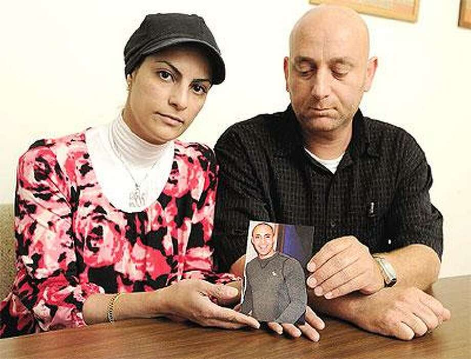 Loryan and Basem Karzoun sit in their lawyer's office in West Haven with a picture of their son, Jafar, who died after being punched by another student on campus. (Peter Casolino/Register)