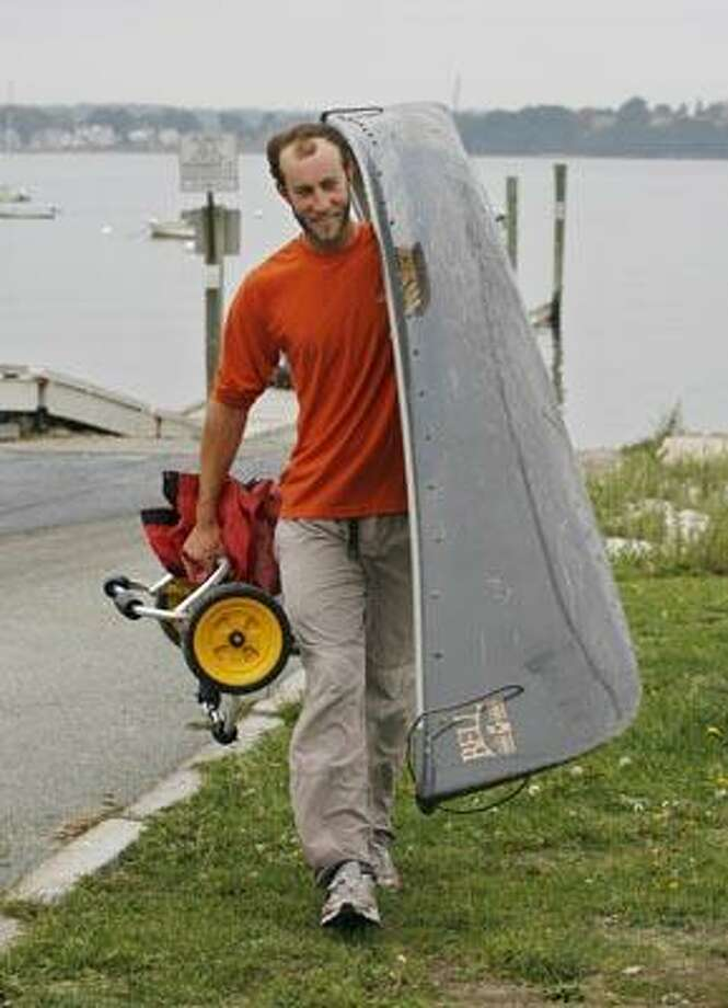 Alexander Martin, 24, of Kensington, Conn., carries his canoe Friday, Sept. 24, 2010 in Portland, Maine after completing a 4,300 mile cross-country canoe trip from Portland, Ore. to Maine. Martin says that his entire trip was human powered, either by paddle or or by towing the canoe with a bike. (AP Photo/Joel Page) Photo: AP / FR23211 AP