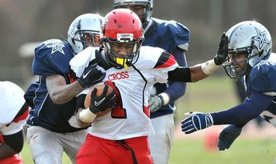 New Haven--  Wilbur Cross' James Ward battles for yards as Hillhouse's  William Glover, left and Darrin Dixon make the stop defends during second quarter.    Photo by Peter Casolino/New Haven Register   11/25/10 Cas101124
