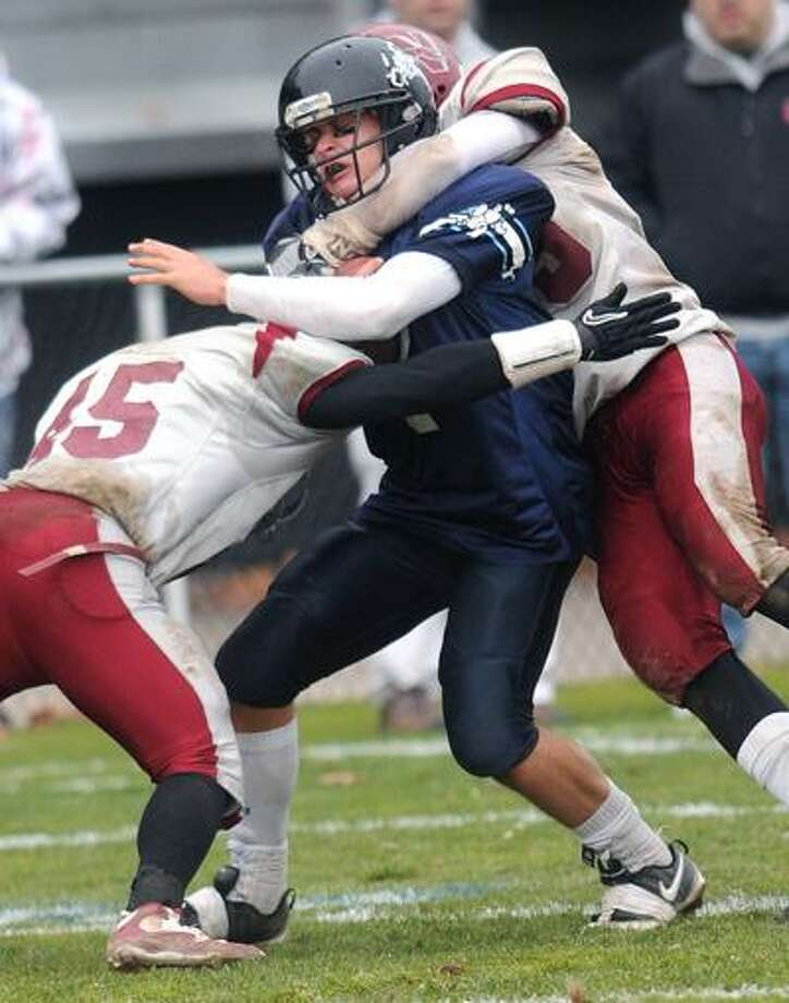 Ansonia--Ansonia quarterback Elliot Chudwick is brought down by Naugatuck tacklers Jordan Grice, left, and Mike Giugno, right.  Photo by Brad Horrigan/New Haven Register-11.25.10.