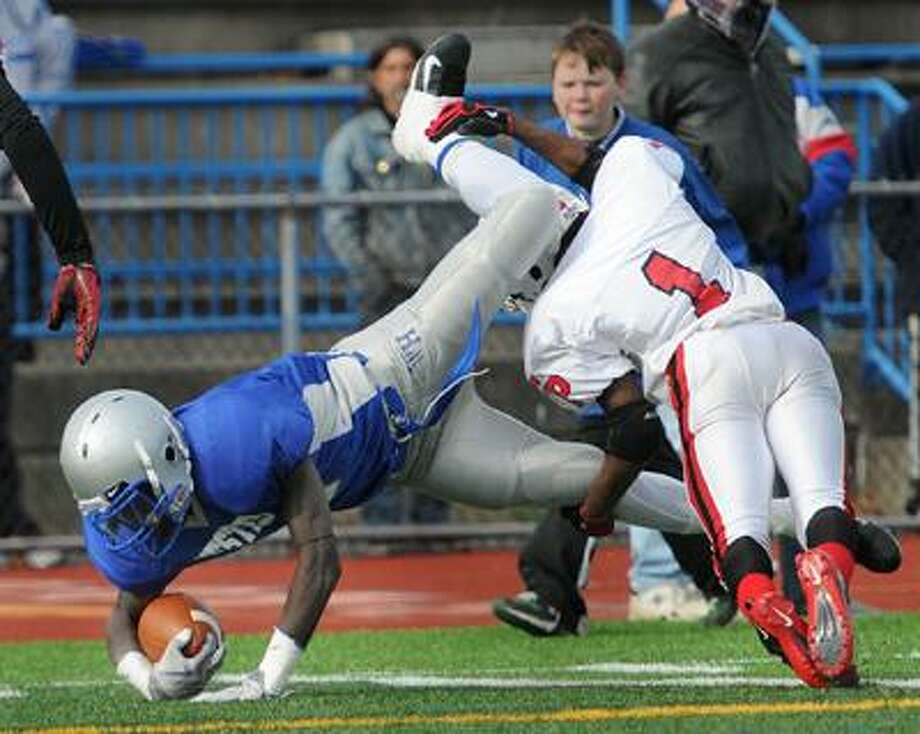 West Haven--West Haven running back Ervin Philips is tackled by Fairfield Prep defensive back Myles Gaines during Thursday's game in West Haven.  Photo by Brad Horrigan/New Haven Register-11.25.10.