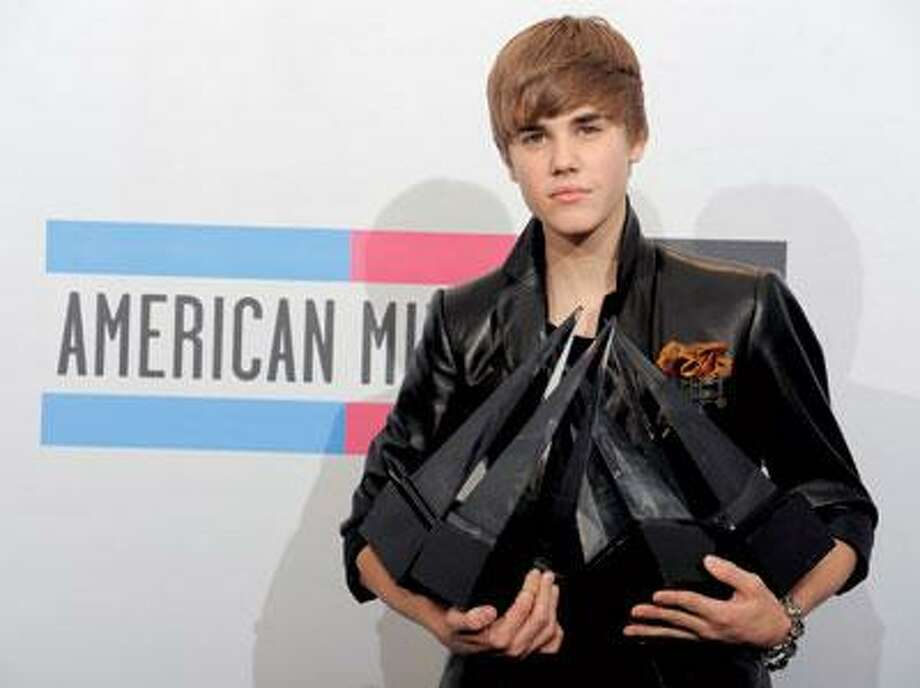 Justin Bieber hold his awards backstage at the 38th Annual American Music Awards on Sunday. (Associated Press)