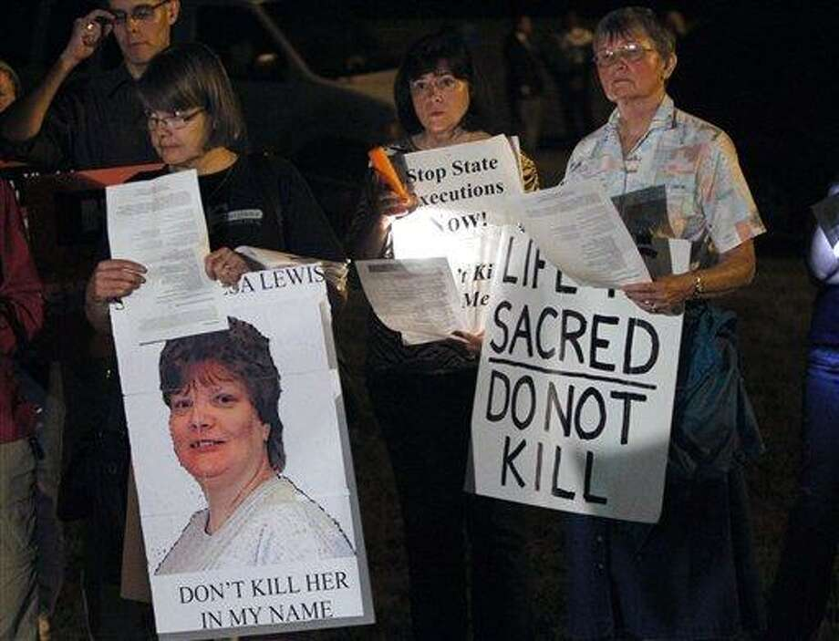 Death penalty protestors hold signs as they protest the execution of Teresa Lewis outside the Greensville Correctional Center in Jarratt, Va., Thursday, Sept. 23, 2010. Teresa Lewis was executed and pronounced dead at 9:13 p.m. (AP Photo/Steve Helber) Photo: AP / AP