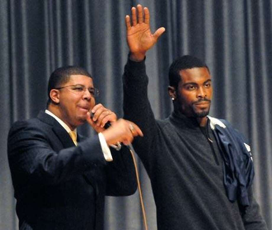 New Haven--Philadelphia Eagles quarterback Michael Vick says farewell to students at Hillhouse High School Tuesday morning about taking good care of animals.  At left is school principal Kermit Carolina.  Photo by Brad Horrigan/New Haven Register-11.23.10.