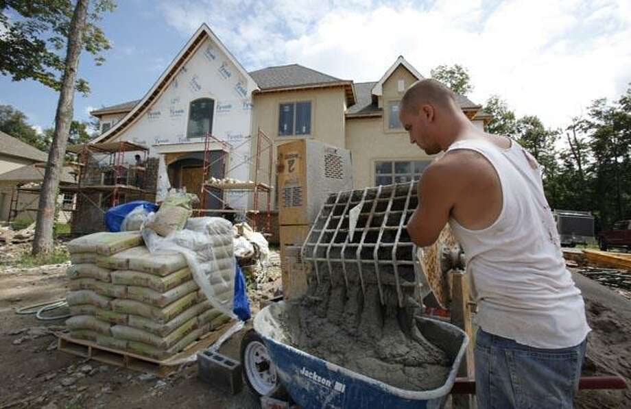 In this Aug. 25, 2010 photo, Andrew VanDusen mixes cement for a new home under construction in Clarence, N.Y. Housing construction surges 10.5 percent in August, as applications for building permits rise.(AP Photo/David Duprey) Photo: AP / AP