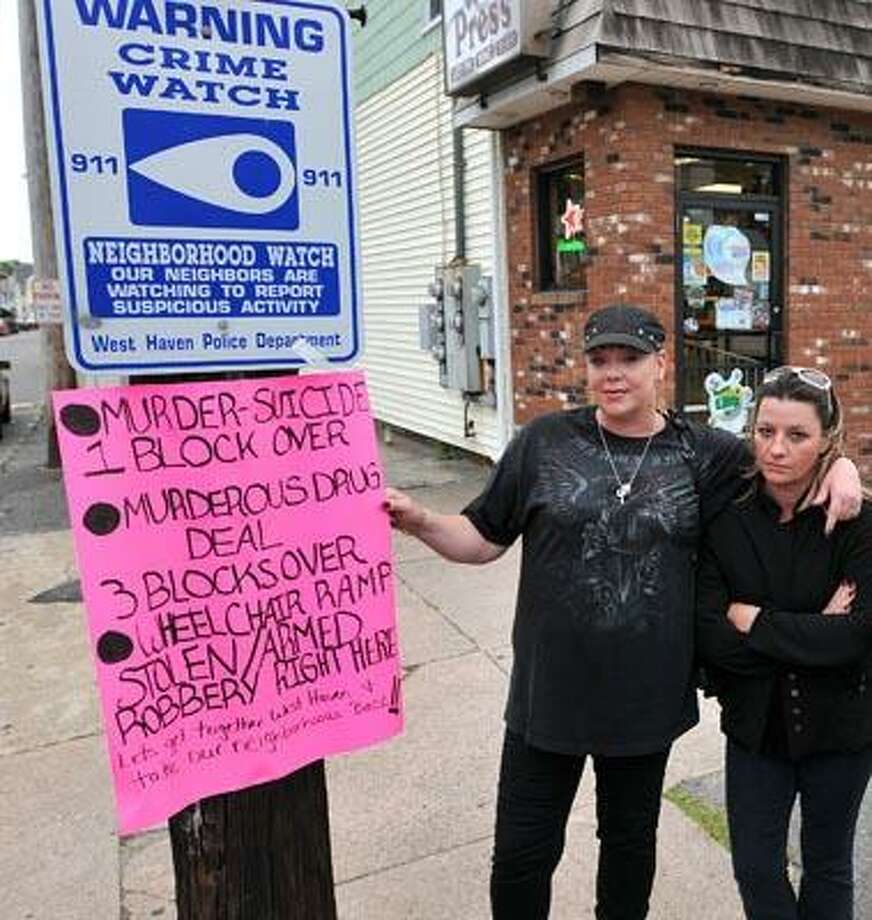 West Haven residents Joanne Cari, left, and Norine Cozza are drawing attention to the recent crime wave that has gripped the area near 191 Campbell Avenue near the Wine Press Liquor store. Someone placed a sign on the corner describing some of the recent crimes in the area. (Peter Casolino/Register)