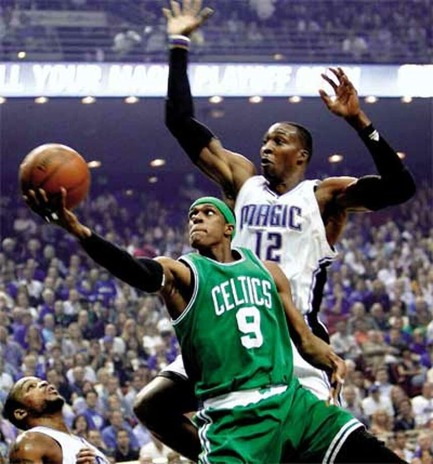 The Celtics' Rajon Rondo drives in for a shot past Magic center Dwight Howard in Tuesday's game. The Celtics won 95-92 to take a 2-0 series lead. (Associated Press)