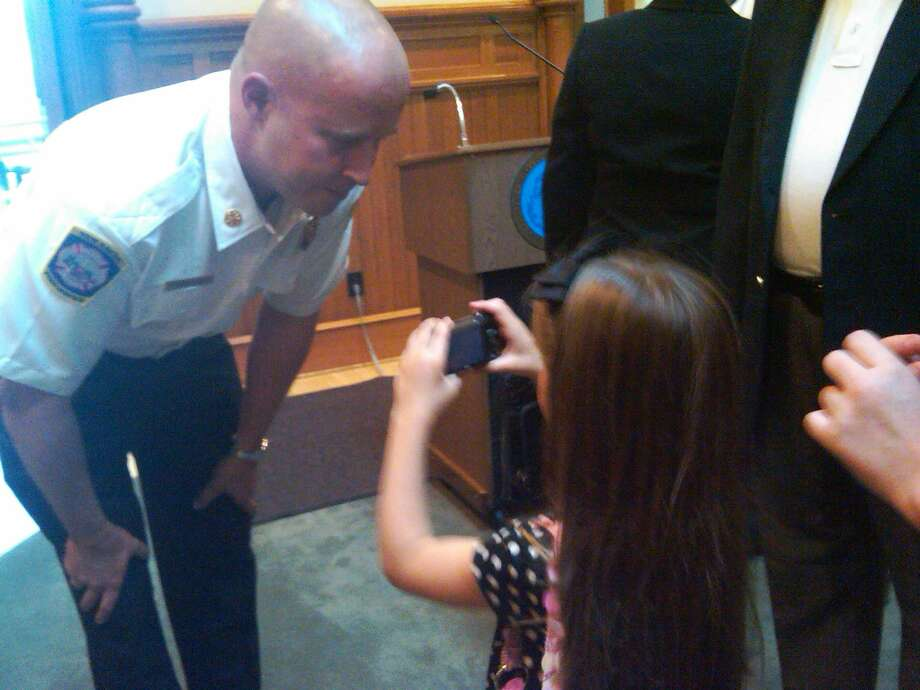 Patrick Egan, New Haven's new assistant fire chief, speaks to his daughter, Maggie, as she snaps a photo of him at his swearing in ceremony Wednesday at City Hall Photo by William Kaempffer