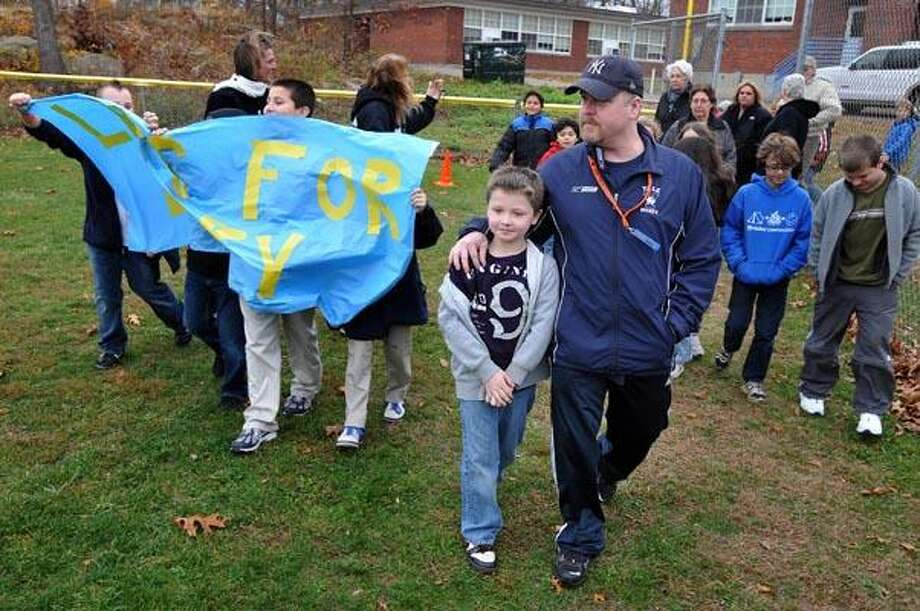 "East Haven-- Larry Paquin walks with one of his sons, Justin (age-8), a third grader at Momauguin School in East Haven, as the school held a ""Laps For Larry"" walk to raise money for him. Larry has a brain tumor and the entire school turned out to raise money for him and his family. Two of Larry's children go to Momauguin School. Photo by Peter Casolino/New Haven Register 11/22/10 Cas101122"