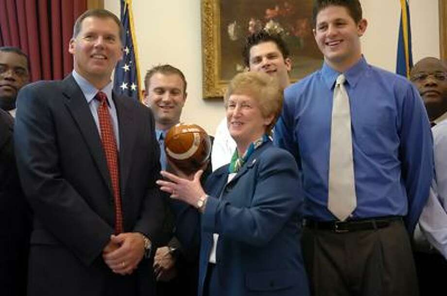 Connecticut Gov. M. Jodi Rell holds the 2004 Motor City Bowl championship game football presented to her by UConn coach Randy Edsall, left, and quarterback Dan Orlovsky of Shelton, during a visit to her Capitol office on March 29, 2005. (Associated Press file photo)