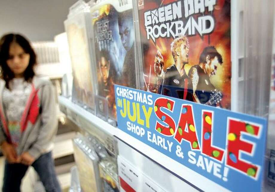 "Video games are among items promoted, Monday, July 19, 2010, for a ""Christmas in July Sale"" at a Toys R Us store in New York. Retailers that pushed holiday sales earlier and earlier to compete for sales during the recession are pumping up the volume still higher at this year's ""Christmas in July"" events. There are sparkly ornaments, images of Santa and strains of holiday music to get shoppers in the spirit. (AP Photo/Bebeto Matthews)"