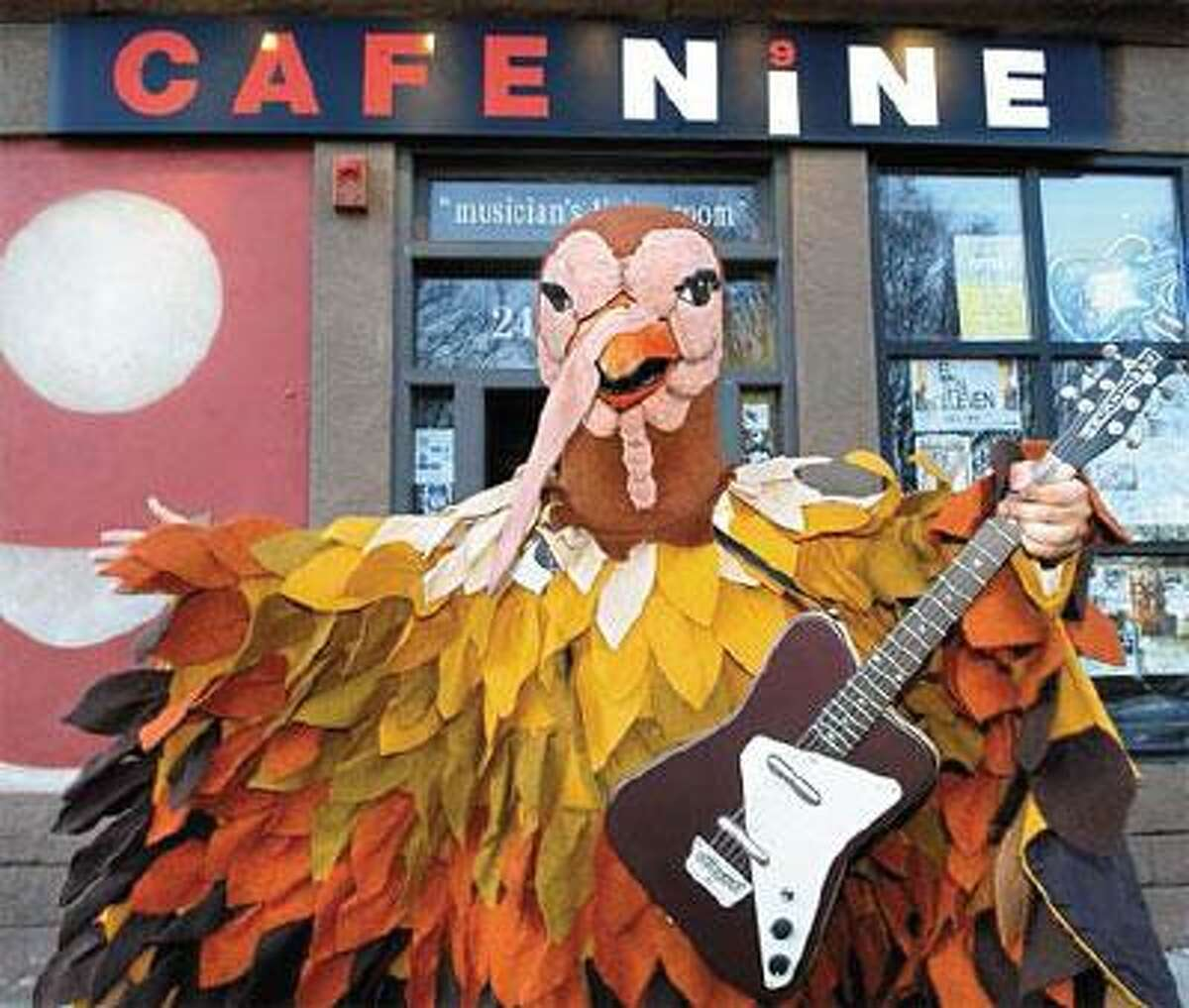 """Dean Falcone is stuffed into a turkey suit outside of Cafe Nine in New Haven, site of Thursday's Thanksgiving Day """"Vomitorium."""" Come Thursday, he'll swap those feathers for a guitar. (Contributed photo)"""