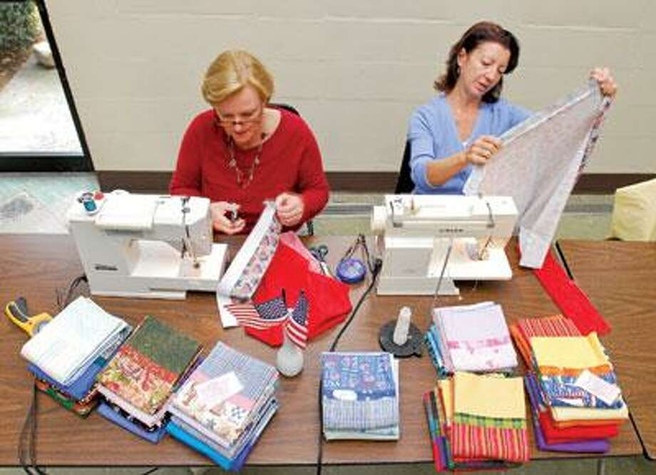 Carolyn Miller (left) and June Evans sew pillowcases for the American troops at Christ the Redeemer Church in Milford. The Connecticut-based group Dream Team Moms has made about 150 pillowcases to be shipped overseas. (Brad Horrigan/Register)