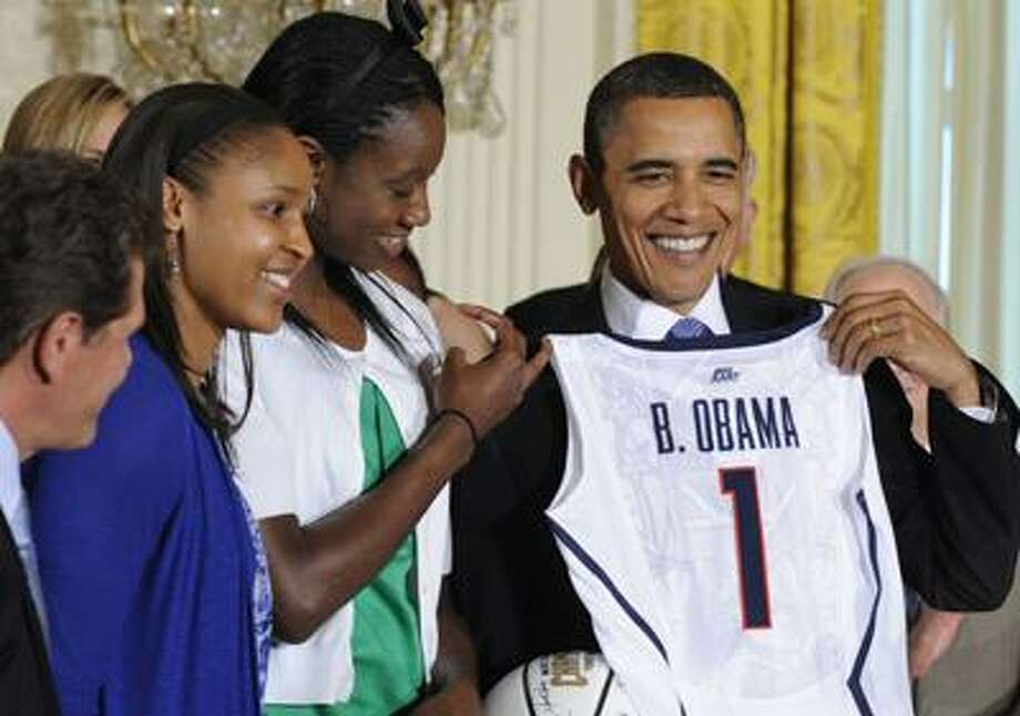 President Barack Obama holds a jersey and basketball that was presented to him by NCAA champion University of Connecticut women's basketball players Tina Charles, in green, and Maya Moore, blue, during a ceremony in the East Room of the White House in Washington, Monday, May 17, 2010. UConn coach Geno Auriemma watches at left. (AP Photo/Susan Walsh) Photo: AP / AP