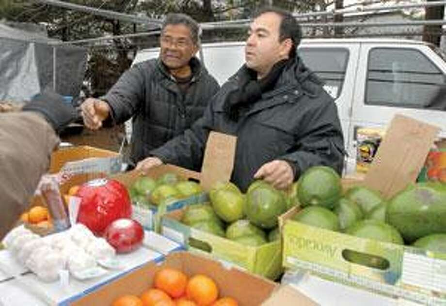Secretary of the state candidate Gerry Garcia, right, helps his father, Felix Garcia, sell food at the Boulevard flea market in New Haven. (Brad Horrigan/Register)