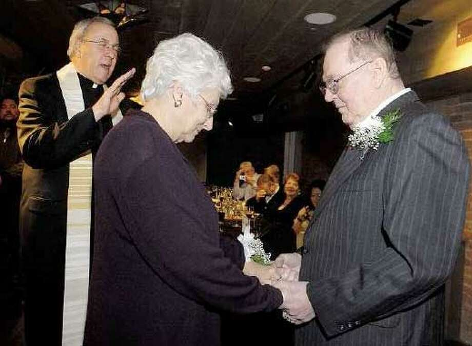(Brad Horrigan/Register) The Rev. Robert Beloin, left, officiates Friday night as Gisele, center, and Yvon Bolduc renew their wedding vows at Geronimo restaurant in New Haven after 50 years of marriage.