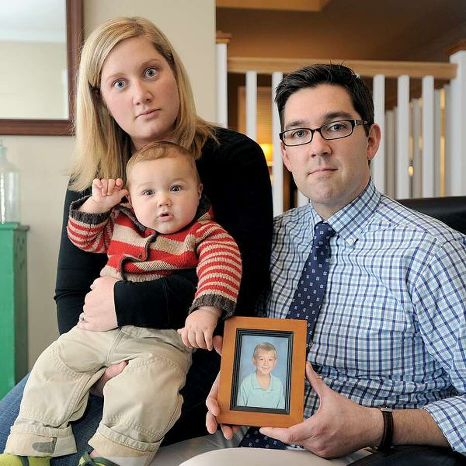 Chris Dall of Guilford, with his wife, Chelse, and their son, Finley, says his ex-wife illegally took his son, Kieran, in photo, to South Africa. (Peter Casolino/New Haven Register)