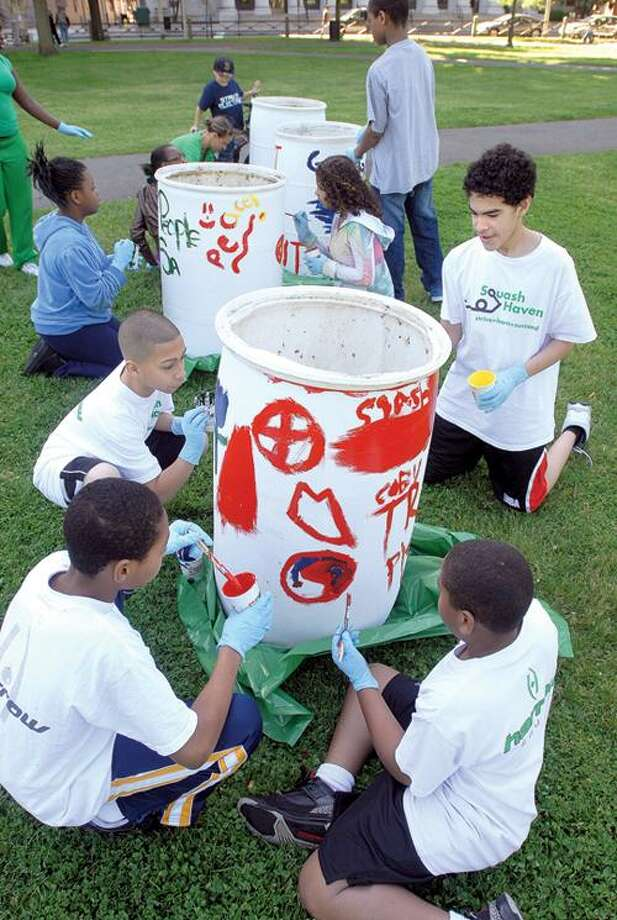 Members of the Squash New Haven after-school program paint garbage cans on the New Haven Green as part of the Town Green Special Services District's community cleanup on the Green Saturday. Painting the can in the foreground are, clockwise from bottom left, Coby Ukadike, 11, Joemar Aviles, 12, Michael Berrios, 14, and Diovanni Prophet, 11. Peter Casolino/Register