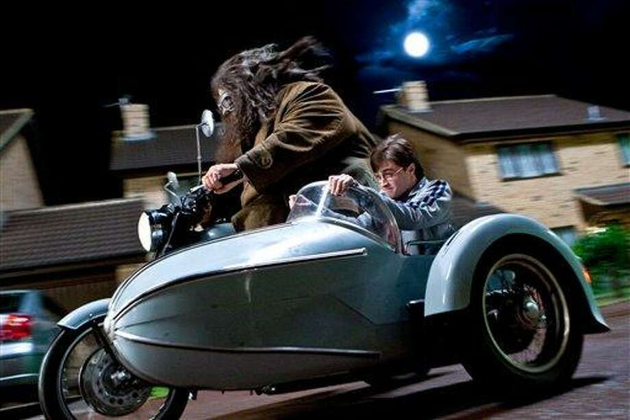 """In this film publicity image released by Warner Bros. Pictures, Robbie Coltrane, left, and Daniel Radcliffe are shown in a scene from """"Harry Potter and the Deathly Hallows: Part 1.""""  (AP Photo/Warner Bros. Pictures, Jaap Buitendijk) Photo: AP / Warner Bros. Pictures"""