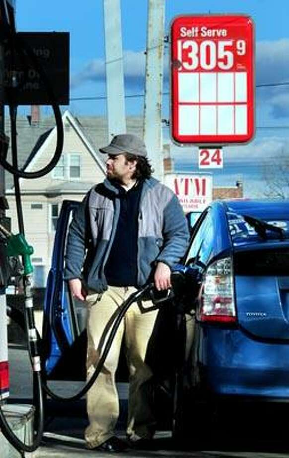 Kristoffer Jensen of Westbrook pumps gas into his car Friday at Best Gas in West Haven. Travelers can expect to pay more at the pumps this year. (Arnold Gold/Register)