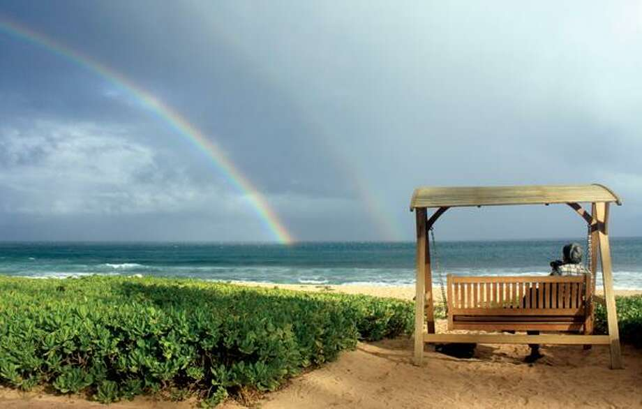 Joseph Heher photographs rainbows at Shipwreck's Beach, Grand Hyatt Kauai in Hawaii. A good way to see the sights, and get your own photo souvenirs, while on vacation is to sign up for a guided photo tour. (AP Photo)