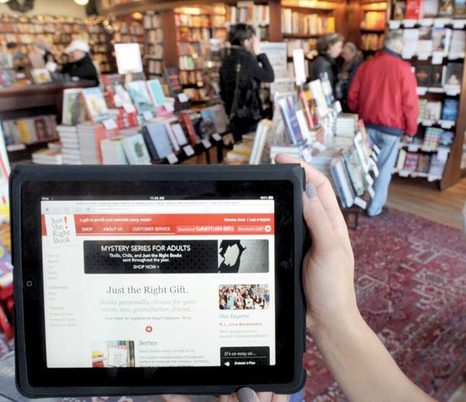 Shana Schneider, vice president and chief marketing officer for the new Just the Right Book website, shows the site off on an iPad. (Mara Lavitt/New Haven Register)