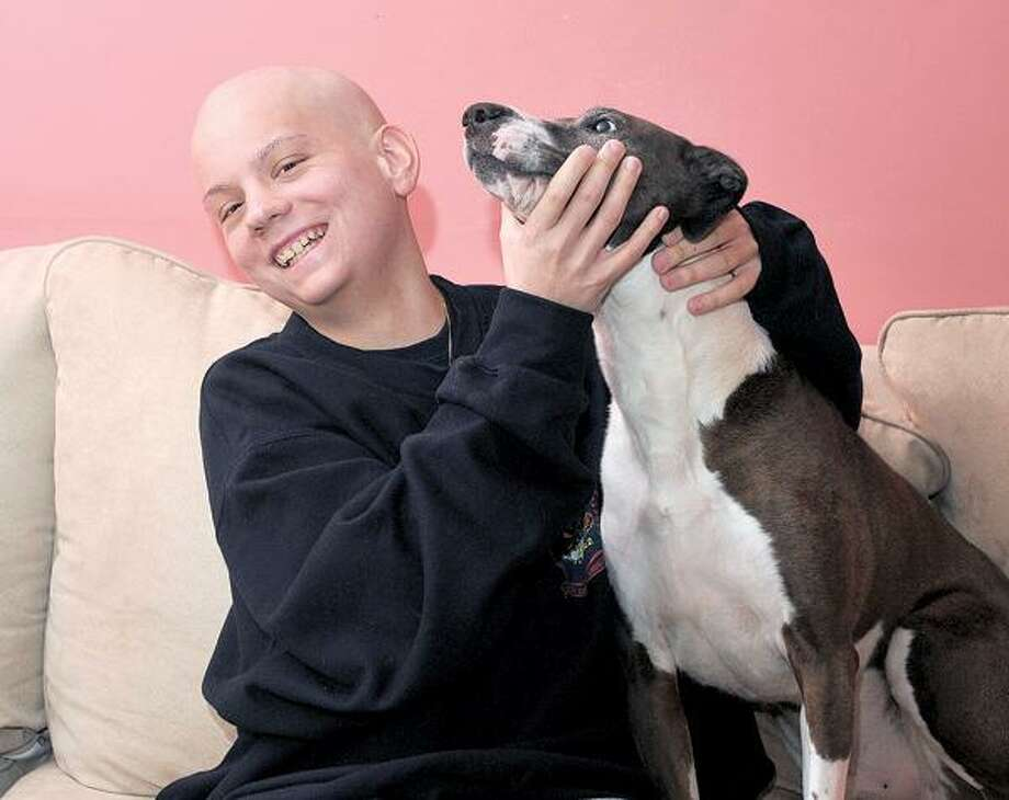 Cancer patient Jordan Jacques, 17, of Hamden plays with his dog, Coco. (Peter Casolino/New Haven Register)