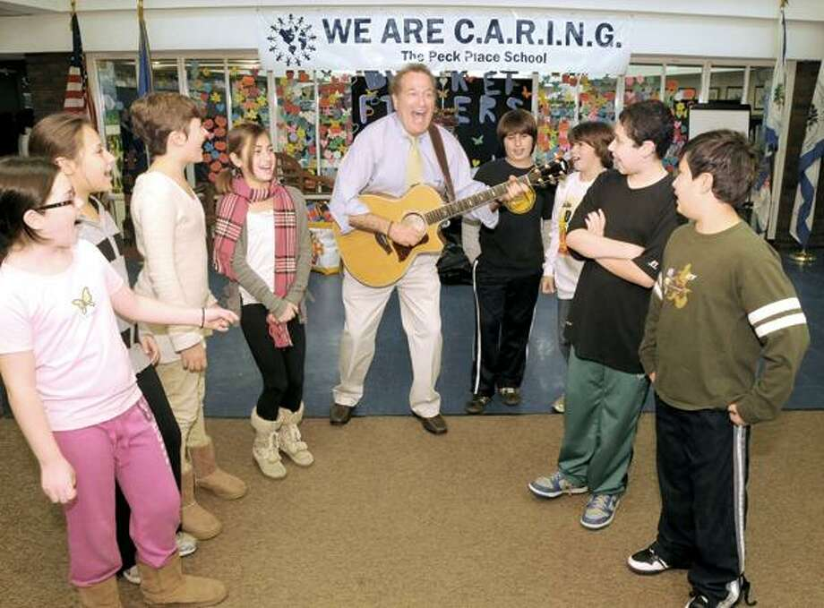 Peck Place School Principal Al deCant performs a song he wrote about caring for, from left, Emily Kilian, Talia Mayerson, Lauren Canna, Hailey Benedetto, Daniel DePalmer, Kyle Beaudette, Pete Vega and Alex Provost. (Mara Lavitt/New Haven Register)