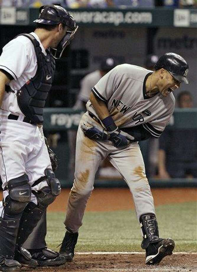 New York Yankees' Derek Jeter, right, screams after being hit with a seventh-inning pitch by Tampa Bay Rays reliever Chad Qualls during a baseball game Wednesday, Sept. 15, 2010, in St. Petersburg, Fla. Looking on is Rays catcher John Jaso. (AP Photo/Chris O'Meara) Photo: AP / AP