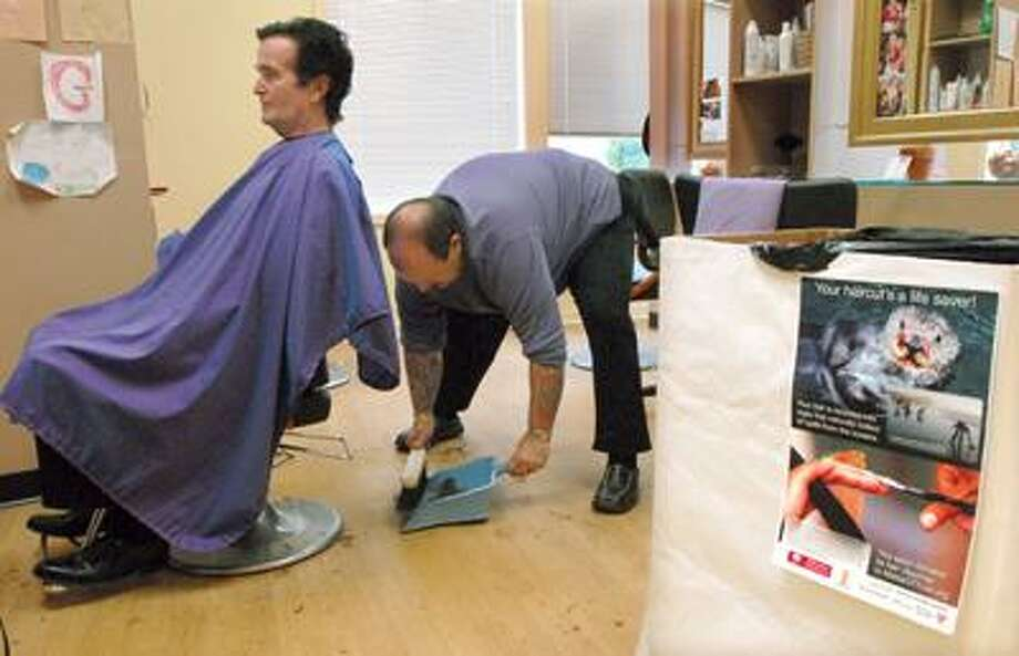 Mark Palumbo Sr., owner of Madison Avenue Salon in Madison, gives Old Saybrook's Edward O'Connor a haircut Wednesday. O'Connor's locks will be added to a collection of hair Palumbo will send to the Gulf Coast to be used in oil-absorbent booms to assist with the oil cleanup. (Mara Lavitt/Register)