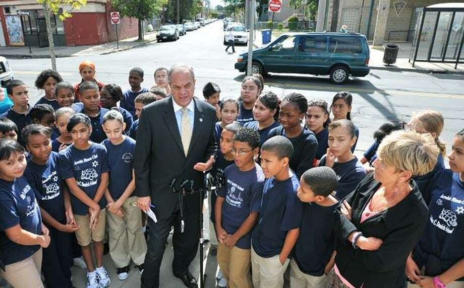 New Haven Mayor John DeStefano Jr. holds a press conference unveiling the Congress Avenue Rehabilitation Project along with 6th graders from John C. Daniels School. Some of the 6th graders there helped with a traffic study of the area near the school. On the right is John C. Daniels Principal Gina Wells. (Peter Casolino/Register)