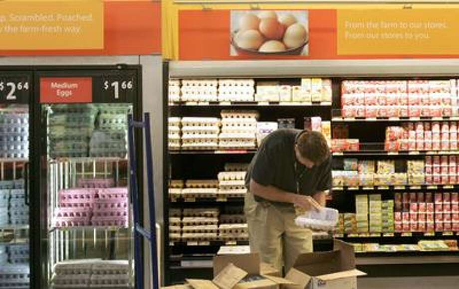 In this April 29, 2008 file photo, a man checks for broken eggs as he stocks the shelves in a Maumelle, Ark., Wal-Mart Supercenter store. Wal-Mart Stores Inc. plans to significantly ramp up its donations to the nation's food banks to total $2 billion over the next five years, the retail giant said Wednesday, May 12, 2010.  (AP Photo/Danny Johnston, file) Photo: AP / AP2008