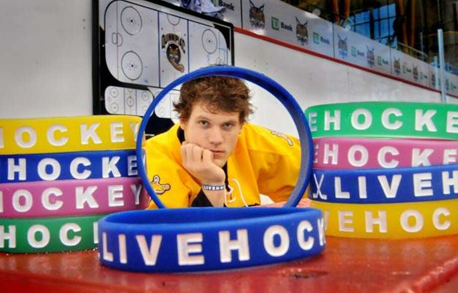 Quinnipiac defenseman, Mike Dalhuisen, with some of the bracelets that he sells to raise funds for cancer research.    Melanie Stengel/Register11/18/10