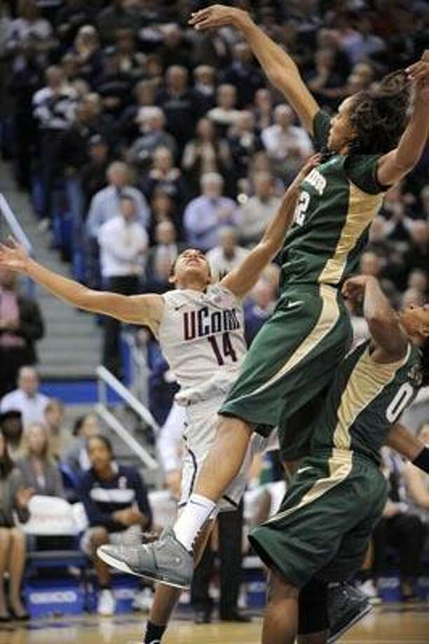 With seconds left in the game, Baylor's Brittney Griner, right, blocks the shot of Connecticut's Bria Hartley in Connecticut's 65-64 victory in an NCAA college basketball game in Hartford, Conn., on Tuesday, Nov. 16, 2010. Griner scored 19 points, had seven rebounds and nine blocked shots. (AP Photo/Fred Beckham) Photo: AP / FR153656 AP