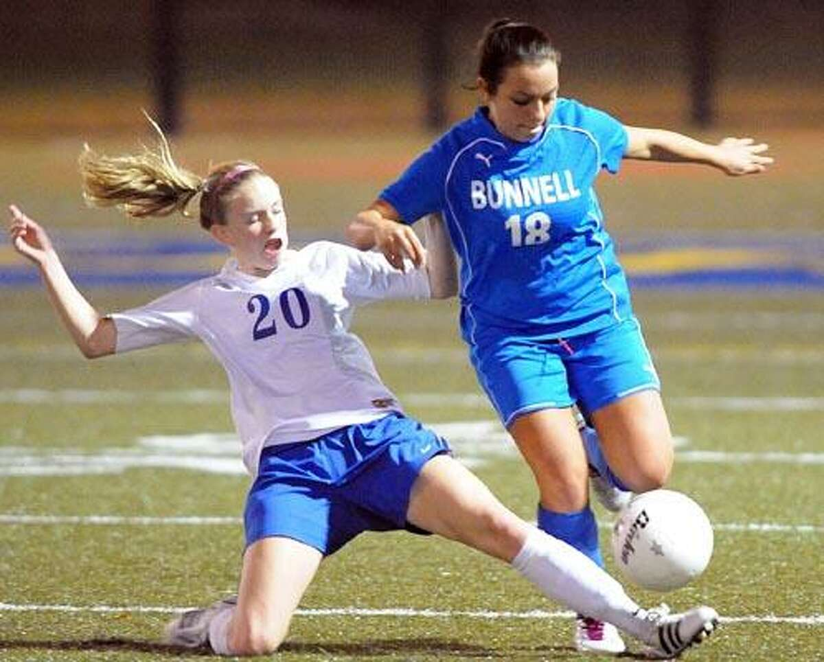 Bunnell's Alana Lorenzo tries to avoid the tackle by Avon's Grace Lennon during the first period. (Photo by Peter Casolino/New Haven Register)