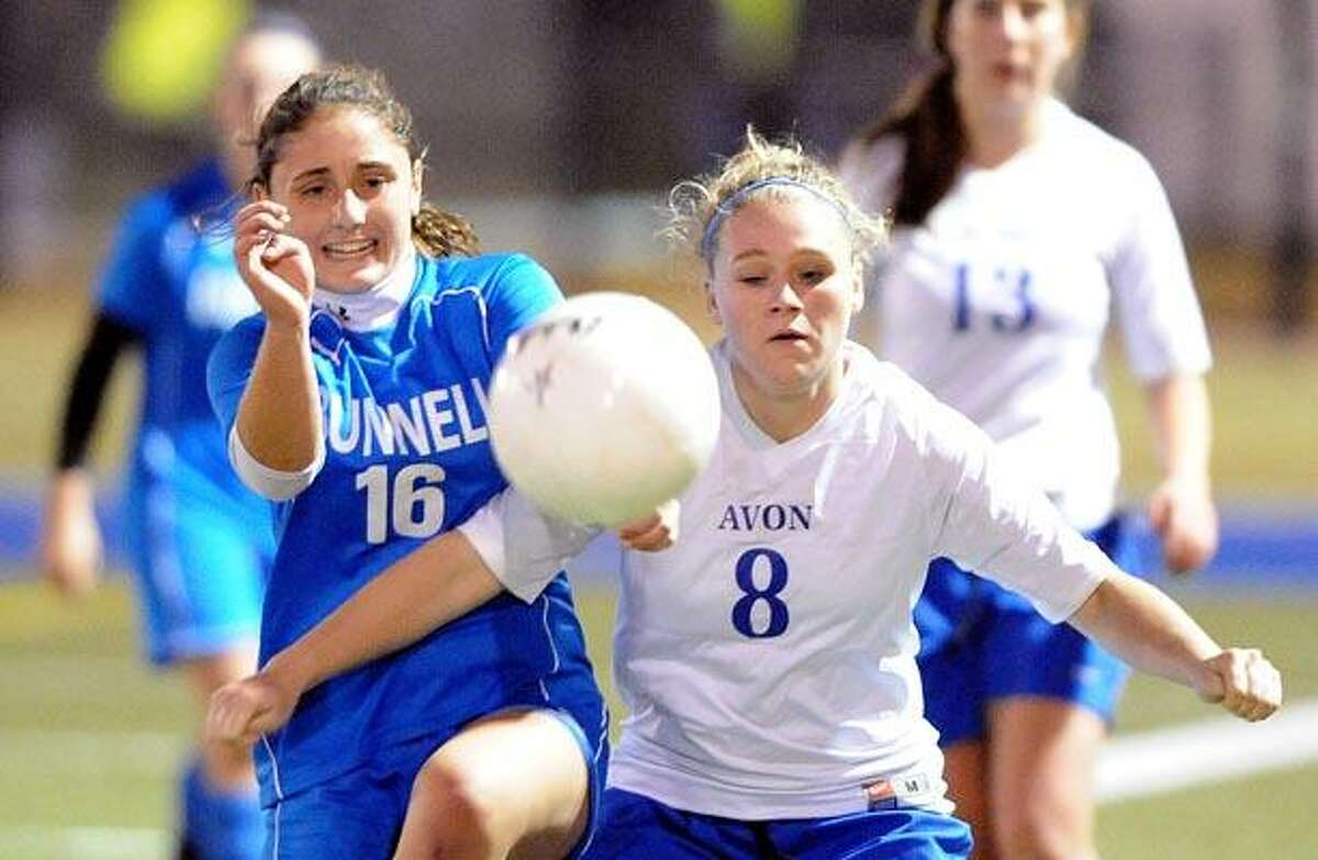 Bunnell's Kacie O'Neil battles for a midfield ball with Avon's Kristina Shayler during the first period. (Photo by Peter Casolino/New Haven Register)