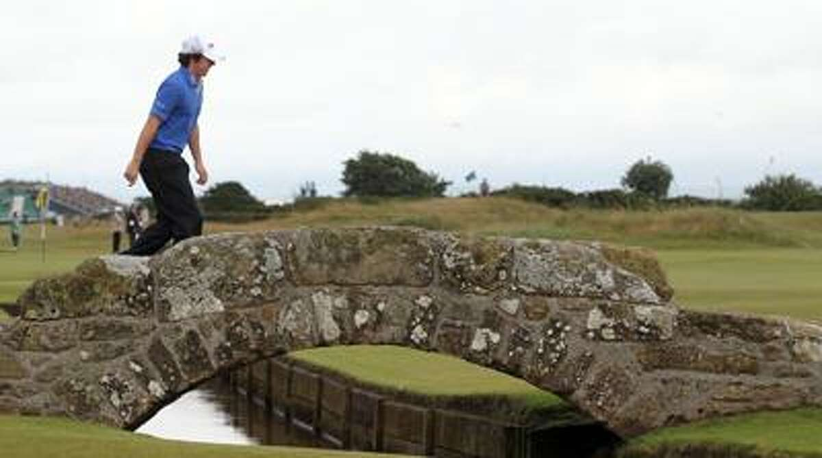 Rory McIlroy crosses the Swilken Burn bridge on the 18th hole of his first-round 9-under 63 during the British Open Thursday on the Old Course at St. Andrews, Scotland. (Associated Press/Peter Morrison)