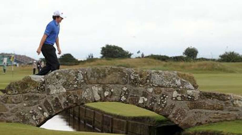 Rory McIlroy crosses the Swilken Burn bridge on the 18th hole of his first-round 9-under 63 during the British Open Thursday on the Old Course at St. Andrews, Scotland. (Associated Press/Peter Morrison) Photo: AP / AP