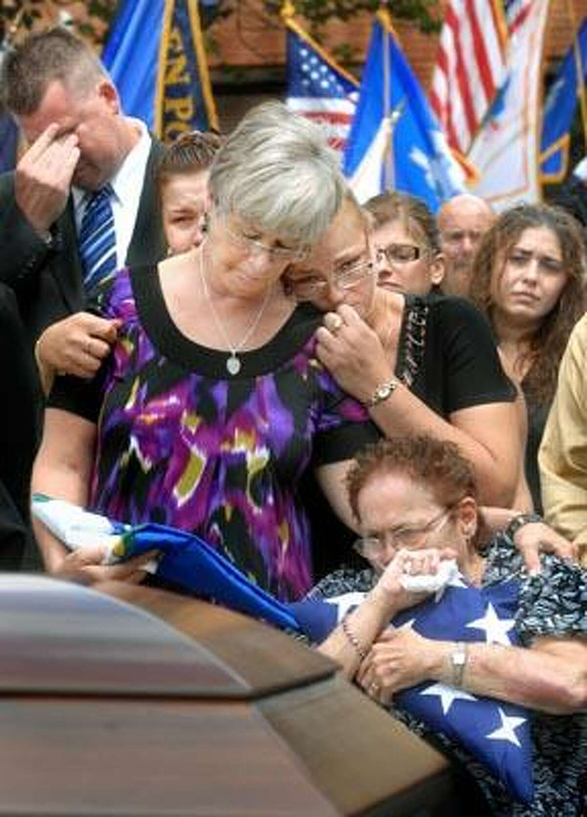People mourn the loss of Shelton police Sgt. Orville Smith, who died after being hit while he was directing traffic July 3. The service was held Tuesday at Shelton High School. (Melanie Stengel/Register)