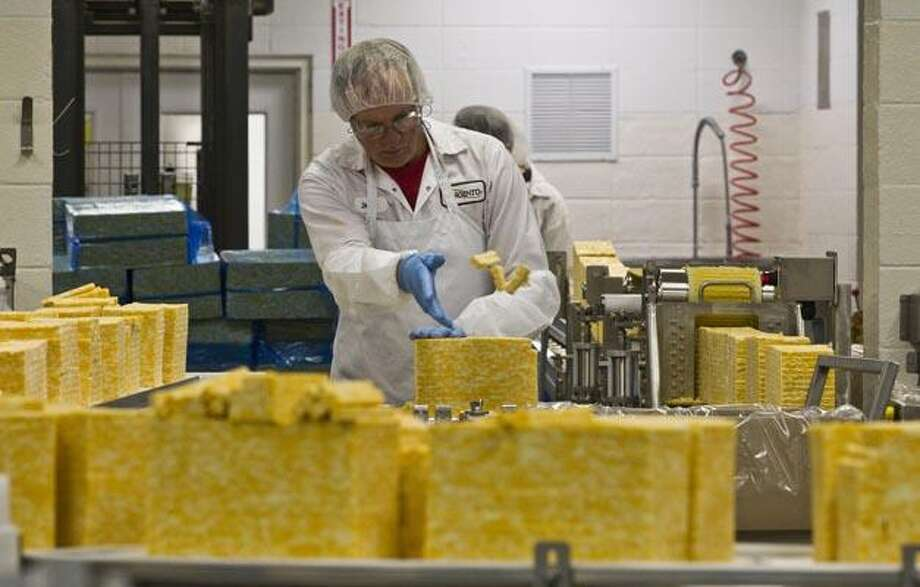 Dennis Schaefer tosses some slices of cheese at the Sargento Cheese Company Friday, Nov. 12, 2010, in Plymouth, Wis. While the sluggish economy has taken a toll on manufacturing and related industries, one sector has remained a bright spot over the last few years: food production. (AP Photo/Morry Gash) Photo: AP / AP